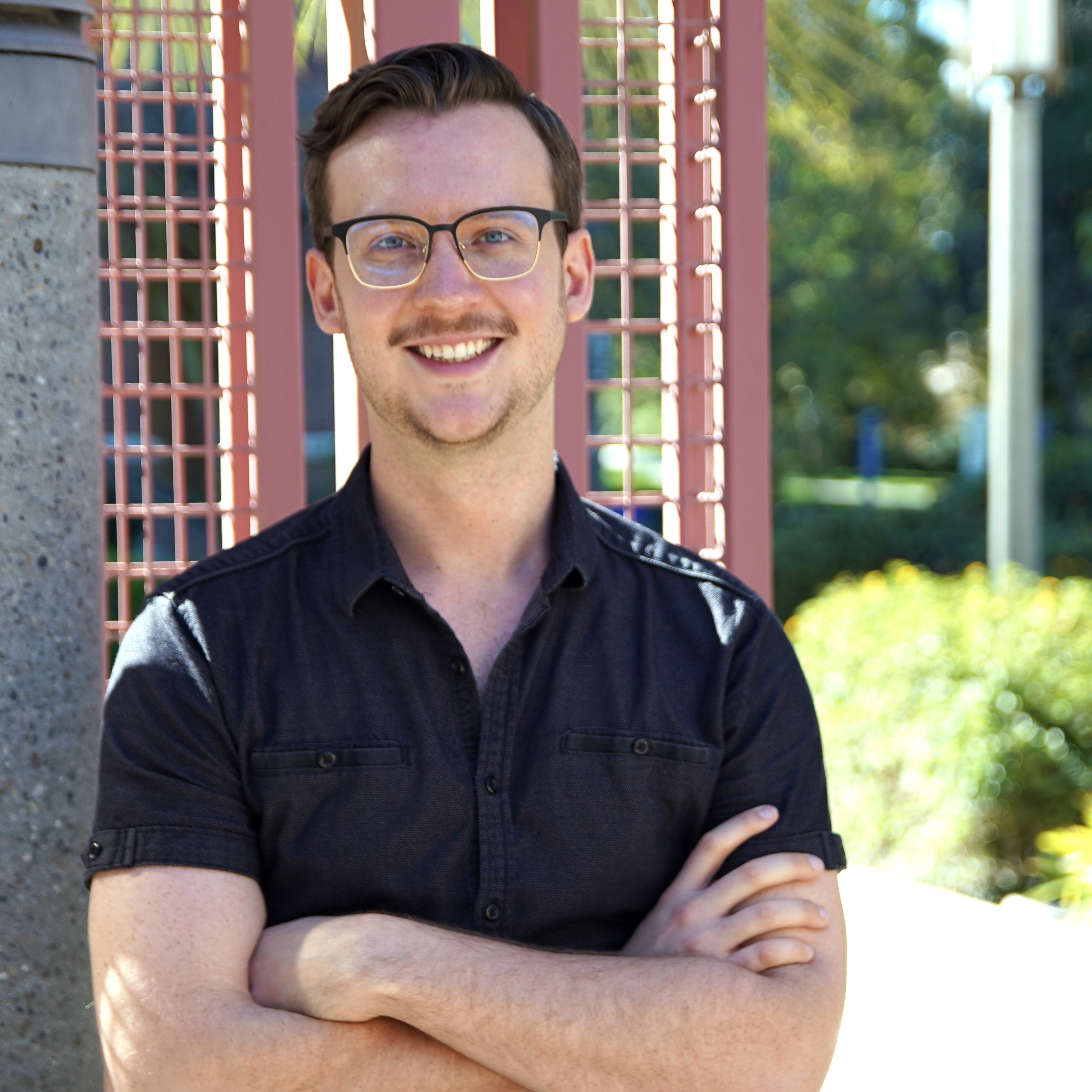 A photograph of me in a black shirt and glasses, with my arms crossed and smiling, in front of a red lattice and bushes outside on UC Irvine's campus.